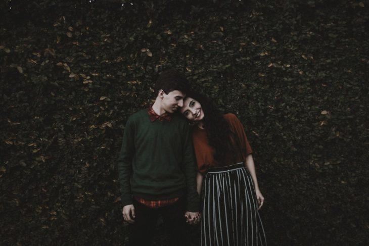 Pareja de novios abrazados, recargados en una pared con plantas