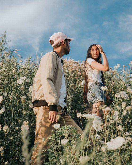 Chico siguiendo a una chica a través de un campo con margaritas
