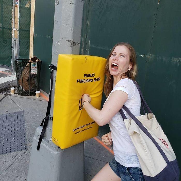 Chica golpeando un saco de box instalado en un poste