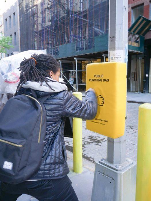 Chica golpeando un saco de box colocado en un poste para que la gente se desestrese