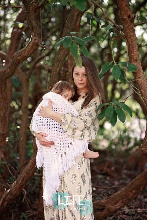 Elora Vianofotografiando a una madre cargando a su bebé mientras usa un vestido amarillo con lentejuelas