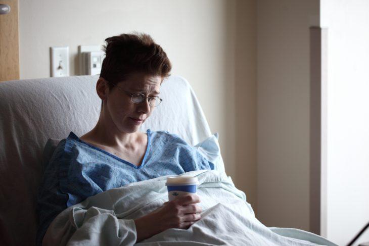 una mujer con lentes en bata azul en la cama de un hospital toma café