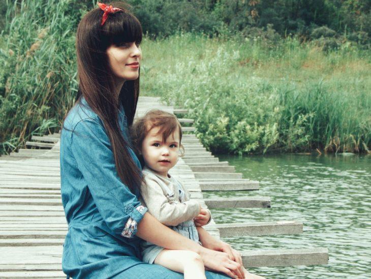 Las tías son como segundas mamás para los sobrinos; chica joven con paliacate en la cabeza y cabello largo y lacio con fleco; cargando a bebé a la orilla de un río