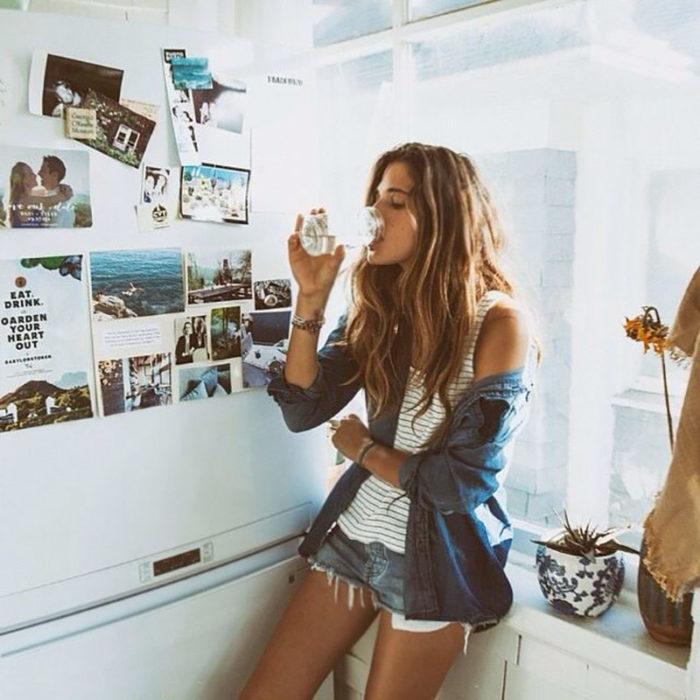 Chica recargada en un mueble de cocina bebiendo agua