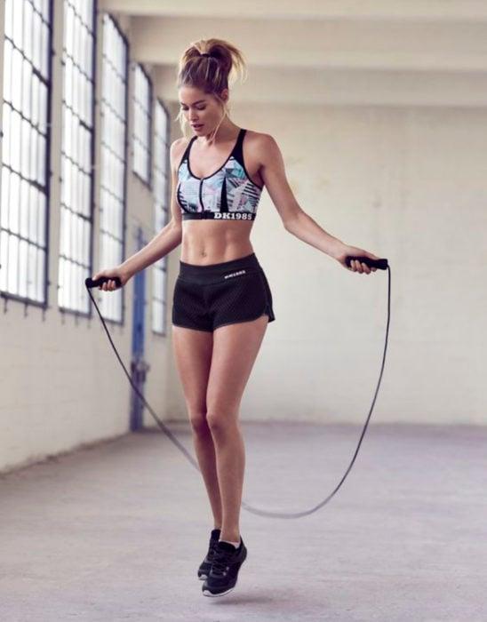 Chica usando ropa deportiva, brincando la cuerda