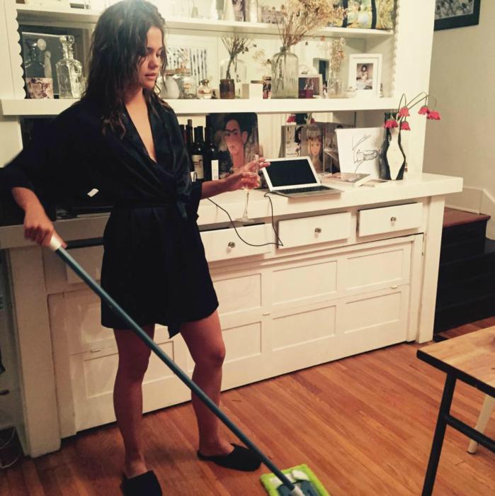 Chica en bata limpiando el piso de su casa