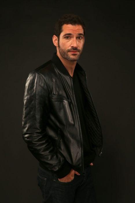 Actor de serie de Netflix, Lucifer, Tom Ellis; hombre con chamarra de cuero y manos en los bolsillos del pantalón