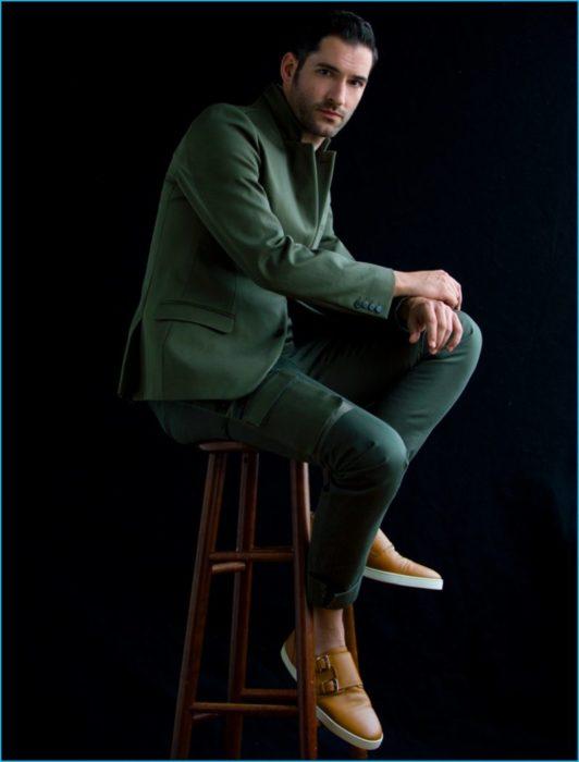 Actor de serie de Netflix, Lucifer, Tom Ellis; hombre sentado en un banco con traje verde