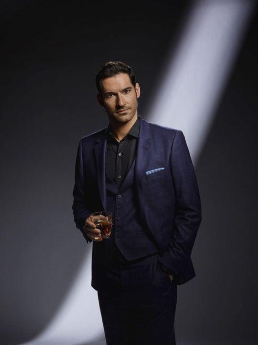 Actor de serie de Netflix, Lucifer, Tom Ellis; hombre sosteniendo un vaso, usa traje azul marino