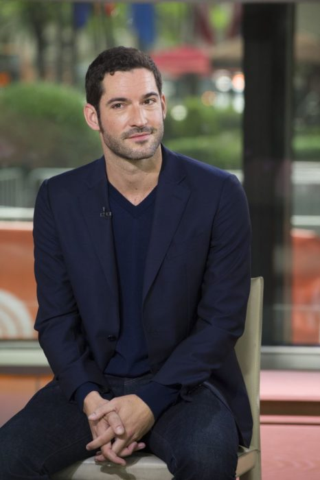 Actor de serie de Netflix, Lucifer, Tom Ellis; hombre de traje azul sentado en una silla