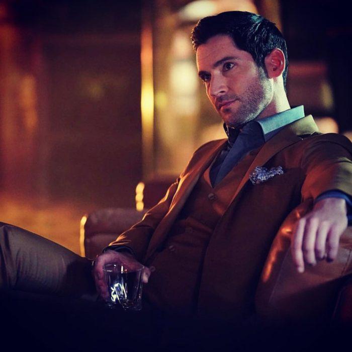 Actor de serie de Netflix, Lucifer, Tom Ellis; hombre de traje café sentado en un sillón sosteniendo un vaso