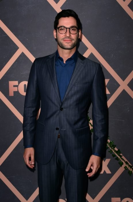 Actor de serie de Netflix, Lucifer, Tom Ellis; hombre con barba, lentes de armazón grueso y traje azul marino