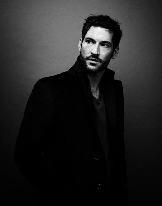Actor de serie de Netflix, Lucifer, Tom Ellis; fotografía en blanco y negro de hombre con barba y gabardina negra