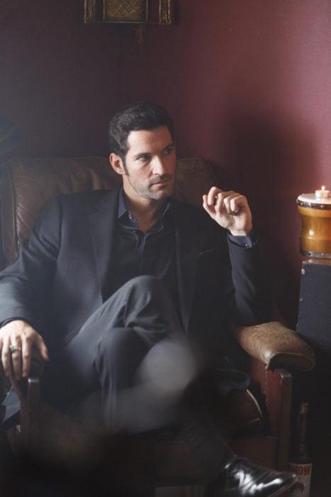 Actor de serie de Netflix, Lucifer, Tom Ellis; hombre con traje sentado en un sillón con las piernas cruzadas