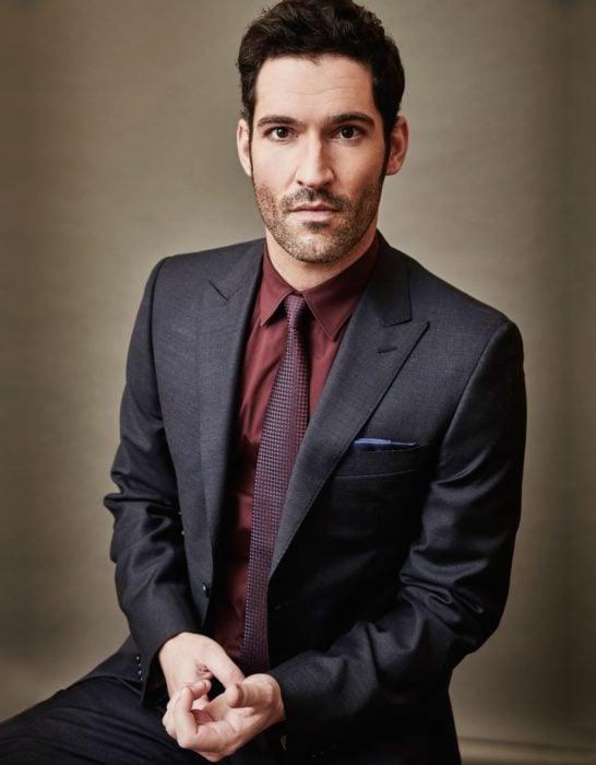 Actor de serie de Netflix, Lucifer, Tom Ellis; hombre con traje gris, camisa guinda y corbata