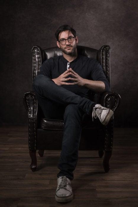 Actor de serie de Netflix, Lucifer, Tom Ellis; hombre de barba y lentes sentado en sillón de cuero con las piernas cruzadas