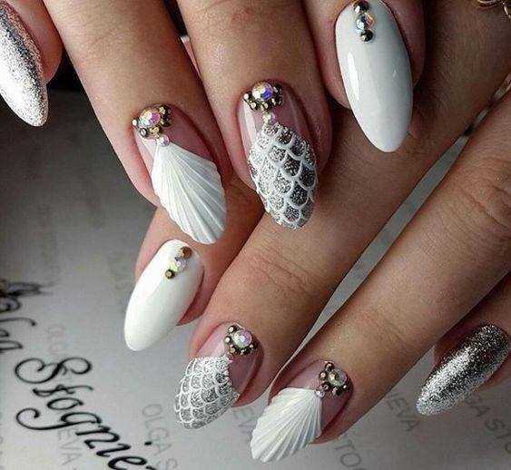 Chica con uñas estilo sirena en color blanco con diseños de miniconchas marinas