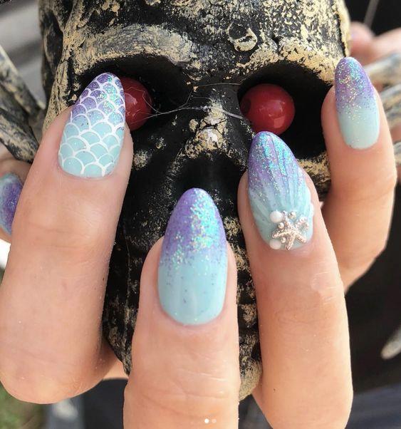 Chica con uñas estilo sirena con efecto espejo en tonos azules
