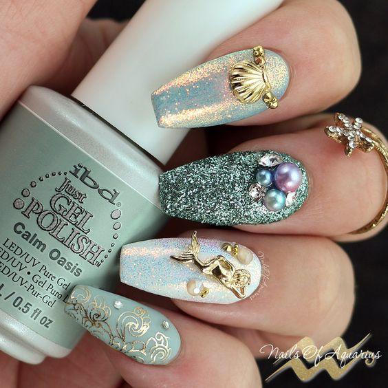 Chica con uñas estilo sirena con decoraciones de conchas y glitter
