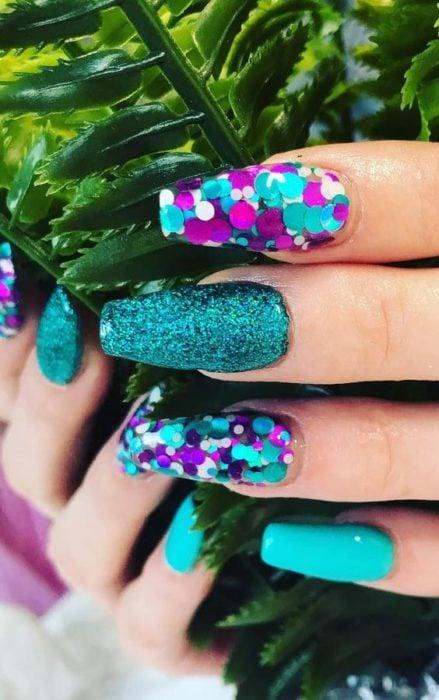 Chica con uñas estilo sirena en tonos morados y verdes