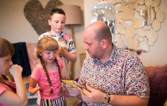 Ben Carpenter lee algo a sus hijos dentro de la casa