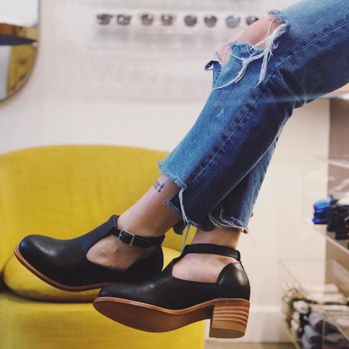 Mujer usando jeans rotos y zapatos con hebilla y tacón alto