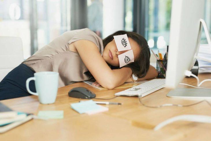 La generación millennial está cansada. Chica inclinada sobre el escritorio