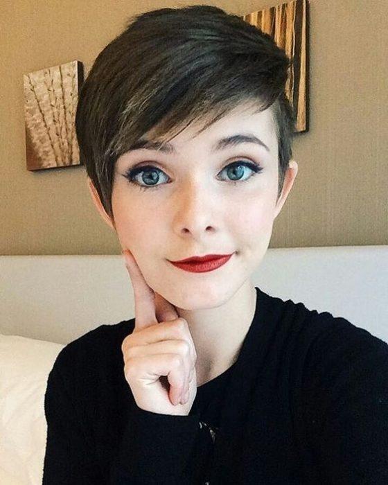 Chica sentada en un sofá tomando una selfie