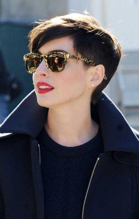 Anne Hathaway usando gabardina, gafas oscuras, caminando por las calles