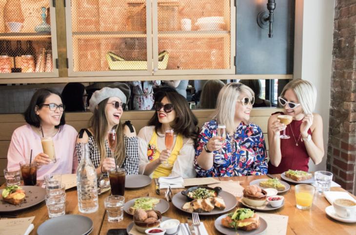 Chicas sentadas en un restaurante desayunando junto a sus amigas