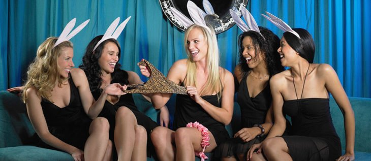 Chicas en un bar vistiendo de negro y con orejas de conejo mientras sujetan un leotardo