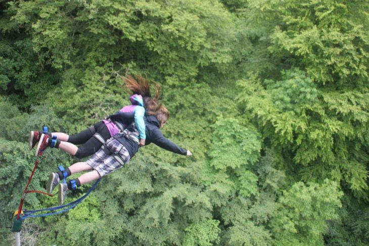 Chicas saltando de un bungee en medio del bosque