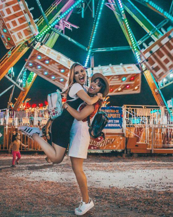Chicas abrazadas delante de una enorme rueda de la fortuna