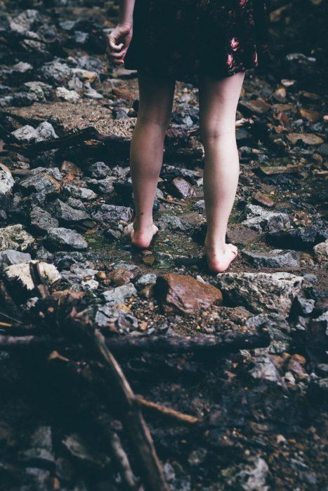 piernas de una mujer que camina por un arroyo con piedras