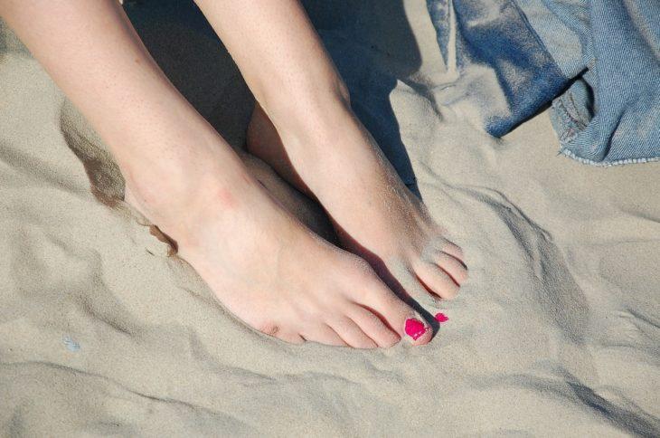 pies de una mujer descalza en la plaza con pintura rosa fuerte en las uñas