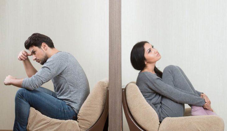 pareja separada por un muro mirando cada uno a su lado