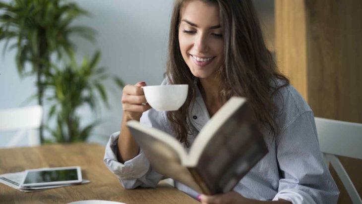 una mujer lee un libro y toma una taza de café