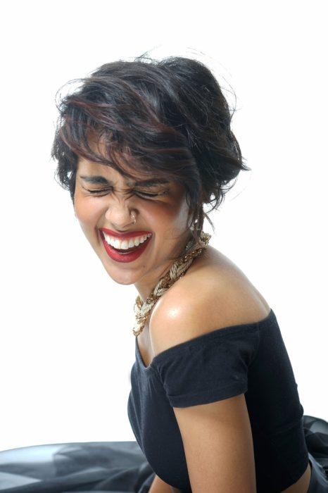 una mujer vestida de negro y pelo corto se ríe