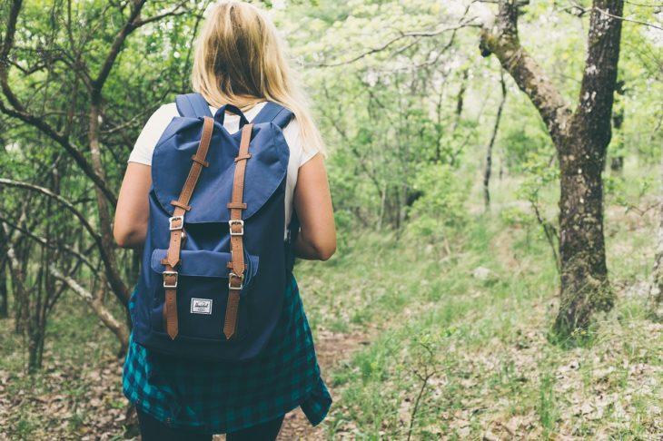 una mujer con una mochila azul camina por un un bosque