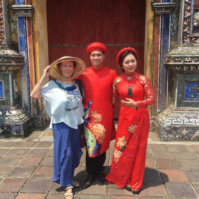 Abuelita mochilera que viaja alrededor del mundo posando con dos personas de China