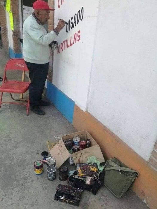 Señor de 79 años pintando la pared de una taquería en la ciudad de México