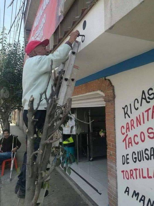 Señor de 79 años pintando un local de comida mientras está sobre una escalera metálica