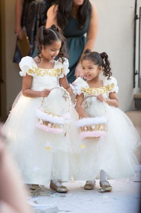 Niñas llevando cestas con flores y vestidos abultados