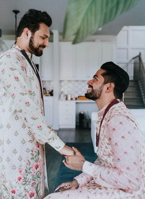 Pareja gay de la india celebrando su boda al estilo hindú. Chico de rodillas sosteniendo la mano de su esposo