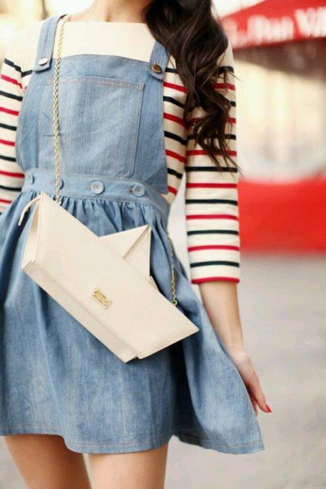 Chica cargando una bolsa en forma de barquillo de papel