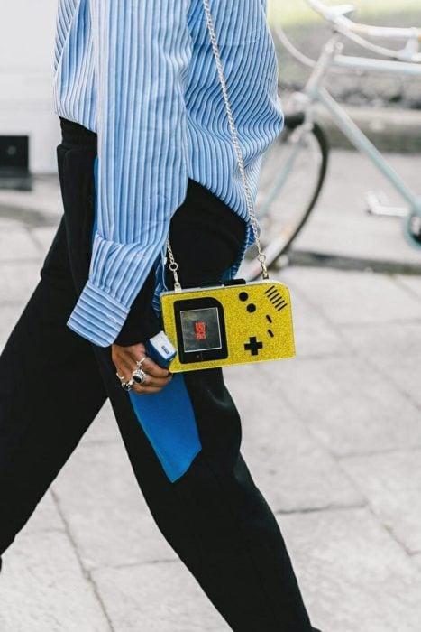 Chica caminando mientras sujeta una bolsa de color amarillo en forma de videojuego