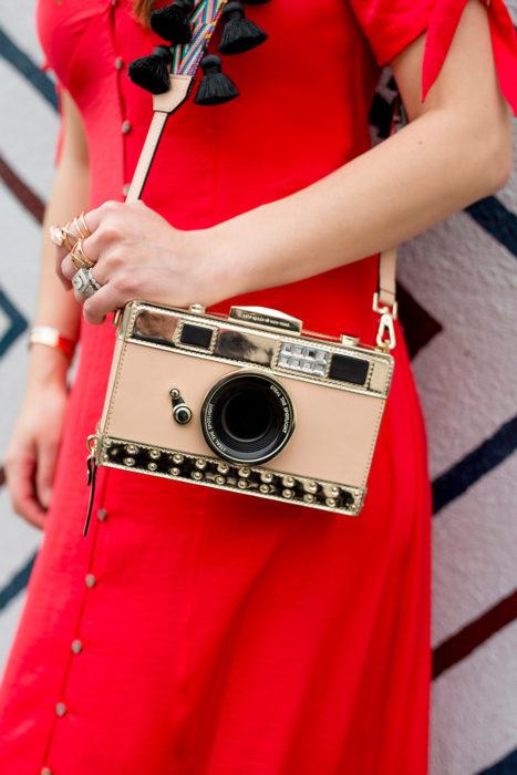 Chica con un bolso en forma de cámara fotográfica