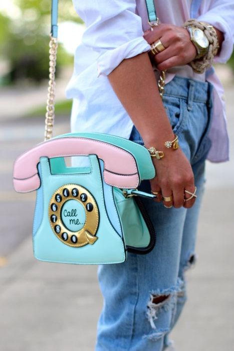 Chica con una bolsa en forma de teléfono de disco