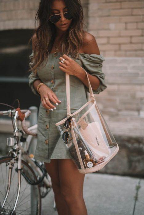 Chica llevando bolso de mano transparente