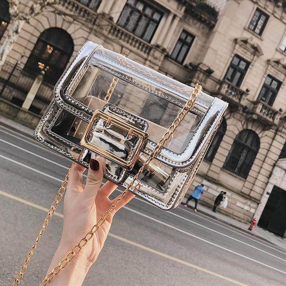 Mano de mujer sosteniendo bolso transparente pequeño con detalles en plateado